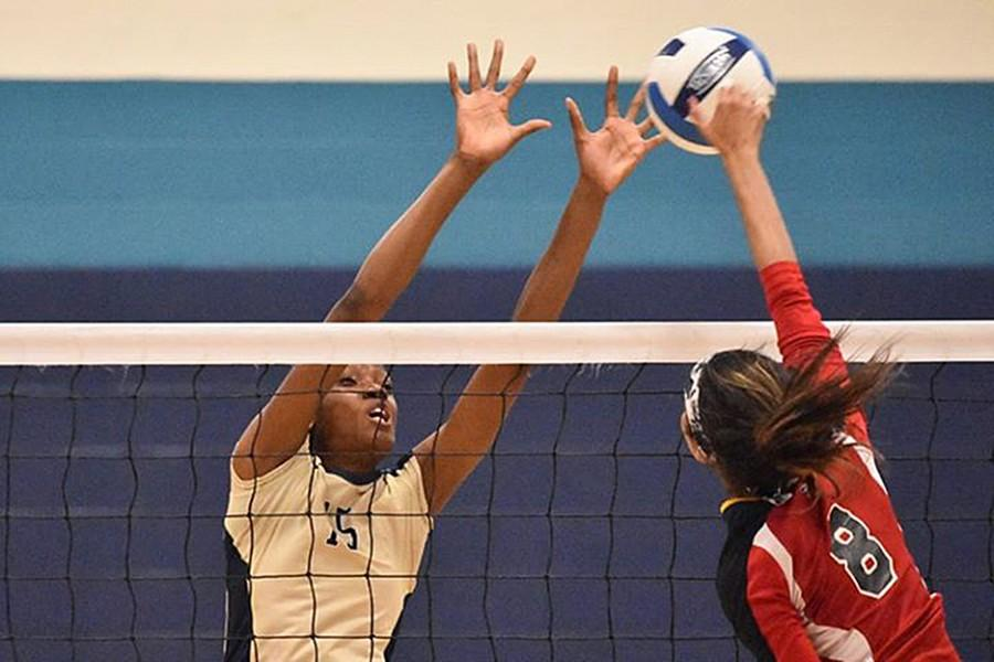 Sharonda Pickering blocks the attempted spike of one of her opponents.