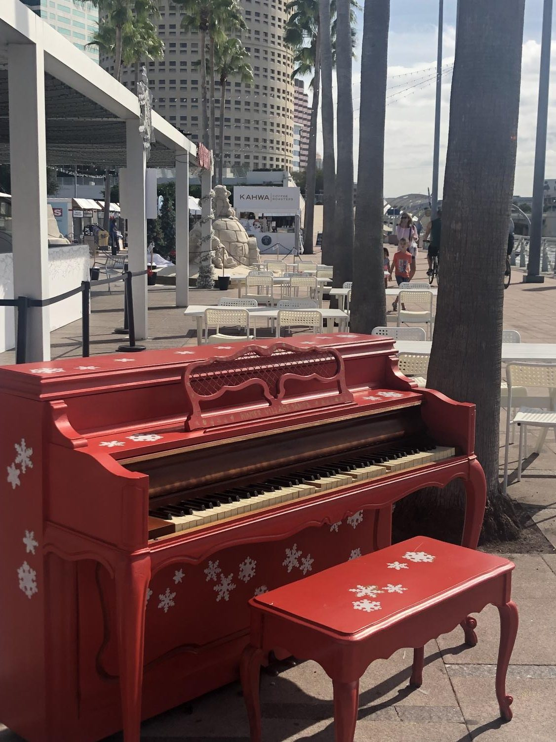 A festive piano at the foreground of the Winter Village at Curtis Hixon Park