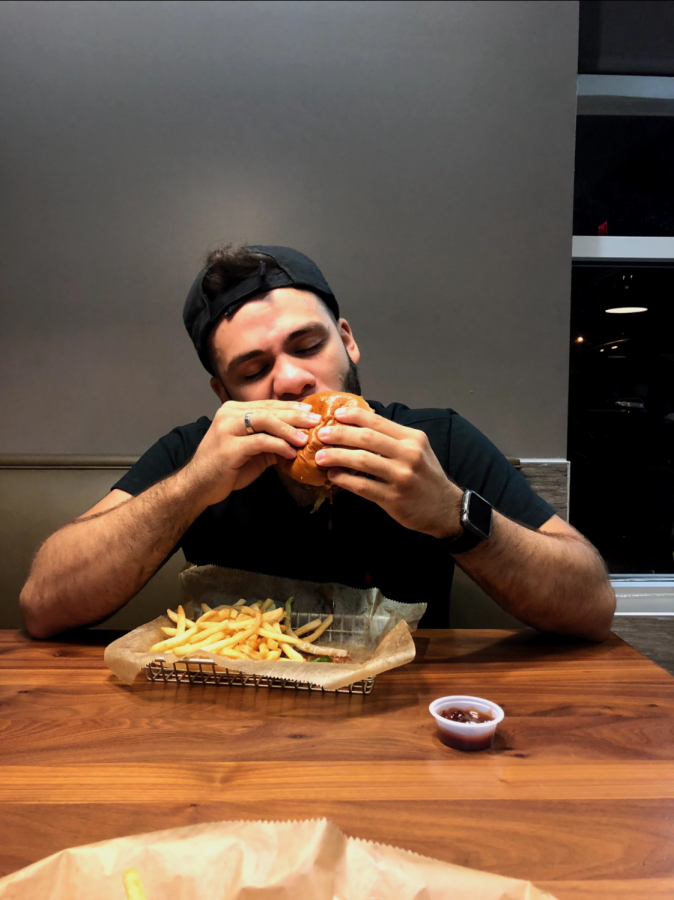 Hawkeye+staff+writer+EliuDaniel+Reyes+enjoys+the+first+bite+of+his+burger.